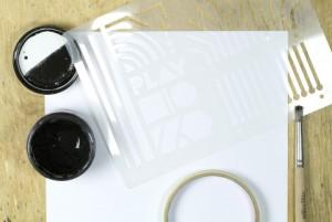 Schablone, Papier, elektrisch leitfähige Farbe, Abdeckband und Pinsel