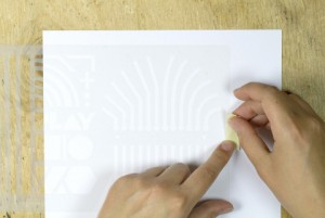Die Schablone wird auf das Papier geklebt